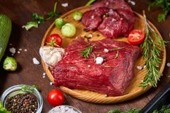 Still life of raw beef meat with vegetables on wooden plate over vintage background, top view, selective focus. Still life of raw beef meat with tomatoes, garlic Stock Photography