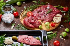 Still life of raw beef meat with vegetables on wooden plate over vintage background, top view, selective focus. Still life of raw beef meat with tomatoes, garlic Stock Image