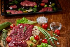 Still life of raw beef meat with vegetables on wooden plate over vintage background, top view, selective focus. Still life of raw beef meat with tomatoes, garlic Stock Photo