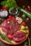 Still life of raw beef meat with vegetables on wooden plate over vintage background, top view, selective focus. Still life of raw beef meat with tomatoes, garlic Royalty Free Stock Images