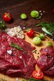Still life of raw beef meat with vegetables on wooden plate over vintage background, top view, selective focus. Still life of raw beef meat with tomatoes, garlic Royalty Free Stock Image