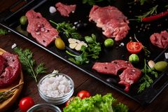Still life of raw beef meat with vegetables on wooden plate over vintage background, top view, selective focus. Still life of raw beef meat with tomatoes, garlic Royalty Free Stock Photography