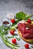 Still life of raw beef meat with vegetables on wooden plate over vintage background, top view, selective focus. Still life of raw beef meat with tomatoes, garlic Royalty Free Stock Photo