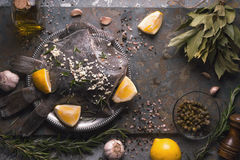 Still life with raw flounders and seasoning on the stone background top view Stock Image