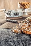 Still life recipe homemade honey ginger oatmeal cookie, pirouette rolled wafer and grain stick on wooden table kitchen. Ferry smoke from pastries in foreground Royalty Free Stock Images