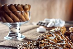 Still life recipe homemade honey ginger oatmeal cookie, pirouette rolled wafer and grain stick on wooden table kitchen. Ferry smoke from pastries in foreground Stock Photo