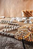 Still life recipe homemade honey ginger oatmeal cookie, pirouette rolled wafer and grain stick on wooden table kitchen. Ferry smoke from pastries in foreground Royalty Free Stock Photography