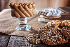 Still life recipe homemade honey ginger oatmeal cookie, pirouette rolled wafer and grain stick on wooden table kitchen. Ferry smoke from pastries in foreground Royalty Free Stock Photos