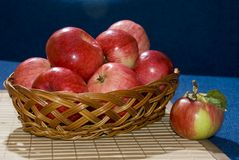 Still life of red apples. Lying in a basket on a blue background Royalty Free Stock Images