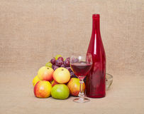 Still-life - red bottle and fruit against a canvas Royalty Free Stock Images