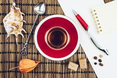 Still life red Cup of tea, spoons. Shells on a wooden table Royalty Free Stock Photos