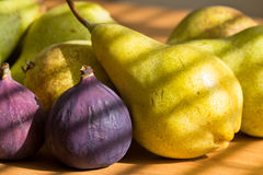 Still life of red figs, green pears. Still life of fresh and fragrant red figs, green pears at the window with the light trap Royalty Free Stock Photos