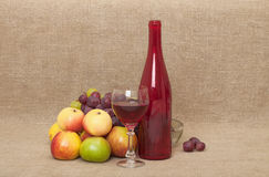 Still-life on red glass bottle, apples and grape Stock Photo