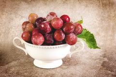 Still life with red grapes in white  vintage cup Stock Images