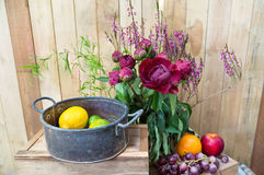 Still life of red peony flowers with fruit on wooden background Stock Photography
