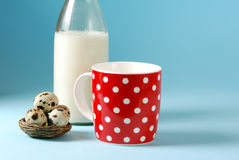 Still life with red, in polka dot, cup of milk, quail eggs and vintage glass bottle Stock Photo