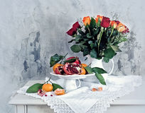 Still life with red pomegranate, orange tangerines and roses Stock Images