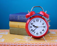 Still life red retro alarm clock and three books Stock Photos