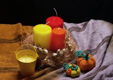 Still life with red and. Yellow candles, and knitted pumpkins Royalty Free Stock Photos