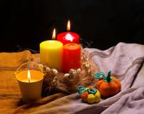 Still life with red and. Yellow candles, and knitted pumpkins Stock Image