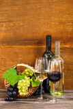 Still life with red and white wine. Bottles and basket with grapes stock photography