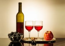 Still life with red wine. A bottle of red wine, two glasses, an apple, and a cup with grapes standing on a table Stock Image
