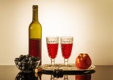 Still life with red wine. A bottle of red wine, two glasses, an apple, and a cup with grapes standing on a table Stock Photo