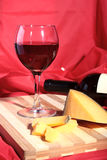 Still life with red wine grapes and chees on wooden table. Stock Photo
