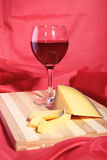 Still life with red wine grapes and chees on wooden table. Stock Images