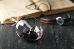 Still life with red wine and old books on the old wooden table in retro style Royalty Free Stock Images