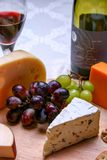 Still life red wine, roquefort cheese, red and green grapes on wooden plate. With bottle Stock Images