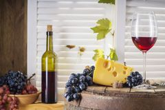 Wine bottle, glass of white wine with cheese and grape. Still life of red wine with wooden keg. Wine bottle, glass of red wine with cheese and grape on a old Stock Photos