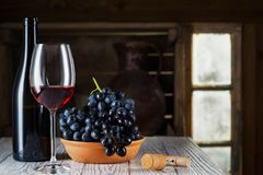 Wine bottle, glass of red wine and grape. Still life of red wine with wooden keg. Wine bottle, glass of red wine and grape on a old wooden barrel. Wine tasting Stock Images