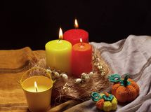 Still life with red and. Yellow candles, and knitted pumpkins Stock Photography