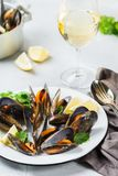 Shellfish mussels with white wine, seafood on a table. Still life, restaurant dinner. Shellfish mussels with lemon and green parsley with white wine. Seafood on Royalty Free Stock Photos