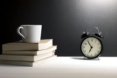 Still life retro alarm clock, cup of coffee on old books. Royalty Free Stock Photography