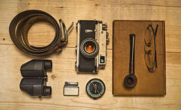 Still life with retro object. Book with compact old camera, compass, cigarette lighter, belt, glasses, pipe, binocular on wood table Royalty Free Stock Photo