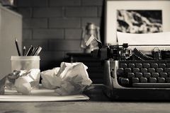Still life of retro office. Telephone, type writer and flower in silver vase place near old lamp on wooden table Royalty Free Stock Image
