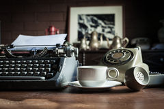 Still life of retro office. Telephone, type writer and flower in silver vase place near old lamp on wooden table Royalty Free Stock Photography