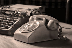 Still life of retro office. Telephone, type writer and flower in silver vase place near old lamp on wooden table Stock Photo