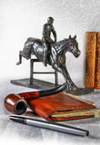 Still life in a retro style with the equestrian's figure. Still life in a retro style with a figure of the equestrian and a tube for smoking Stock Images
