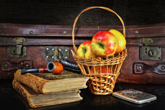 Still life in a retro style with a suitcase and apples. Retro a still life with a suitcase, a tube for smoking, books and with a basket of apples Royalty Free Stock Image