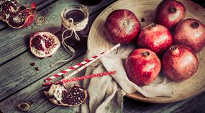 Still life with ripe garnets. On a wooden background Stock Image