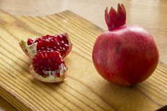 Still life with Ripe Pomegranate on rustic wooden Cutting board Royalty Free Stock Photos