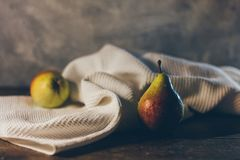 Ripe yellow with red tasty pears on the waffled white towel on the rustic dark brown wooden table and concrete grey bac. Still life ripe yellow with red tasty Royalty Free Stock Images