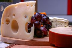 Still life Roquefort, swees cheese and red grapes on wooden plate. 3 types of cheese Stock Images