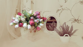 Still life with roses. A bouquet of bright roses on the background of different household items and curtains in the dim light Stock Images