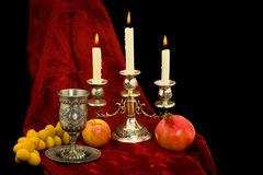 Still-life . Rosh-ha-shana. Still-life with a candlestick, a glass for wine, an apple, dates and a pomegranate Royalty Free Stock Photography