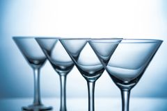 Still life with row of empty martini glasses. On grey royalty free stock photos