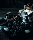 Still life in royal style. Frozen berry of blackberry with silver sugar bowl and spoon on black stone. Stand royalty free stock photo